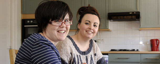 Young carer and girl smiling in kitchen