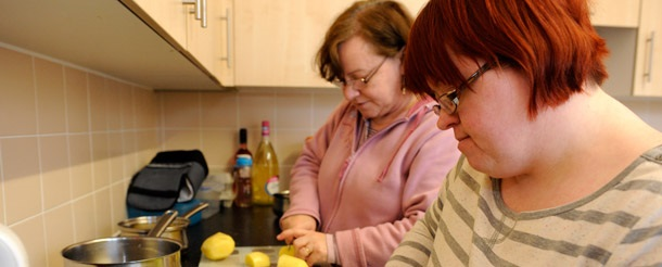 Woman in the kitchen with her carer preparing food